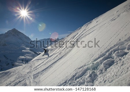 Female skier on downhill race with sun and mountain view with fresh powder near Innsbruck in the Tyrolese Alps, Austria, Europe - stock photo