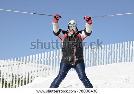 Female skier on the mountain top on a sunny day - stock photo