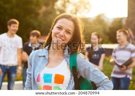 Female smiling student outdoors in the evening with friends - stock photo
