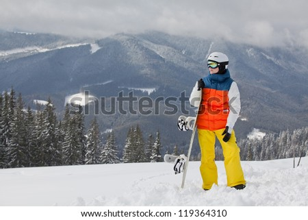 female snowboarder against sun and blue sky - stock photo