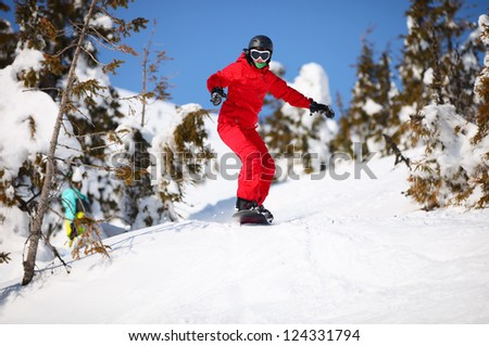 Female snowboarder going to jump on mountain slope - stock photo