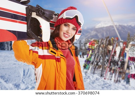 Female snowboarder on top of the winter mountain - stock photo