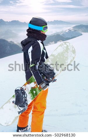Female snowboarder  standing with snowboard in one hand and enjoying alpine mountain landscape - snowboarding concept