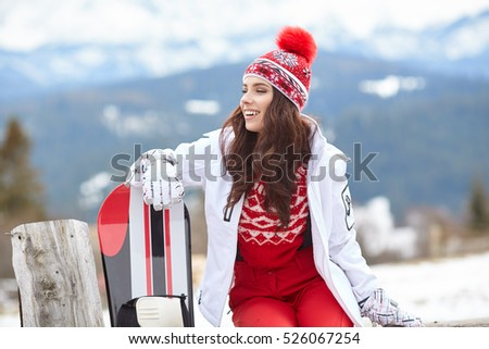 Female snowboarder standing with snowboard in winter resort