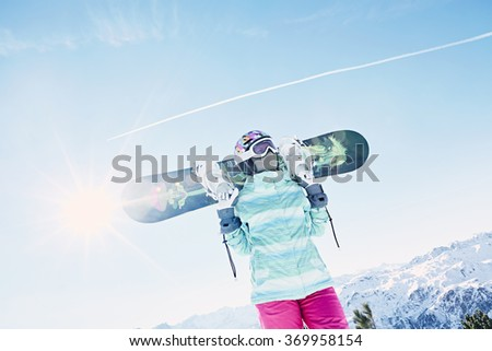 Female snowboarder wearing colorful helmet, blue jacket, grey gloves and pink pants standing standing with snowboard in her hands and preparing for ride - snowboarding concept - stock photo