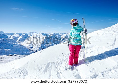 Female snowboarder wearing colorful helmet, blue jacket, grey gloves and pink pants standing with snowboard in one hand and looking at beautiful alpine mountain landscape - winter sports concept - stock photo