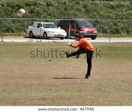 Female Soccer Keeper punts the ball - stock photo