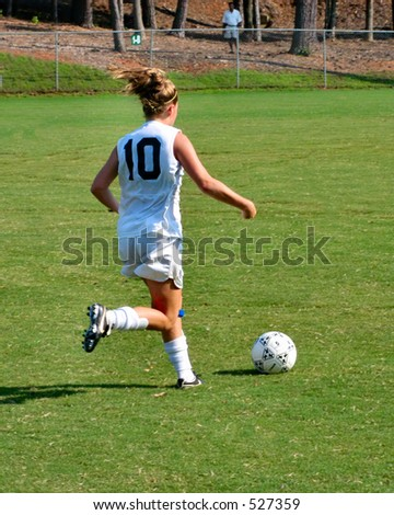 Female soccer player dribbles down field - stock photo
