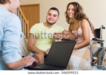 Female social worker consulting smiling woman in invalid chair and husband. Focus on man