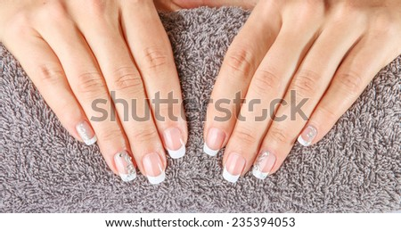 Female soft hands with beautiful french manicure on the towel