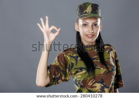 Female soldier in camouflage uniform looks ok sign - stock photo