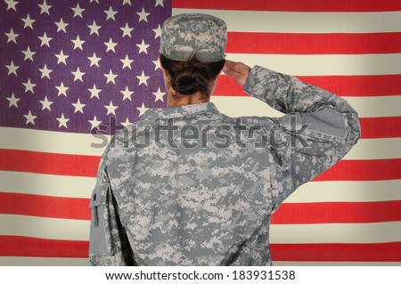 Female Soldier standing in front of and saluting an American flag. Woman is seen form behind only showing her from the waist up. Horizontal format.
