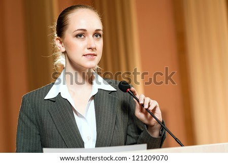 female speaker looks into the room and said into the microphone, speech at the conference - stock photo