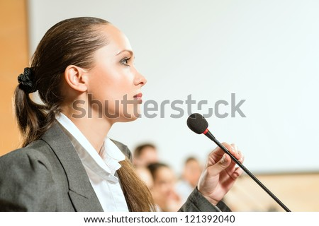 female speaker looks into the room and said into the microphone, speech at the conference