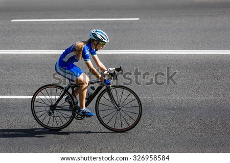 Female sportsman cyclist riding racing bicycle. Woman cycling on countryside road or highway. Training for triathlon or cycling competition. - stock photo