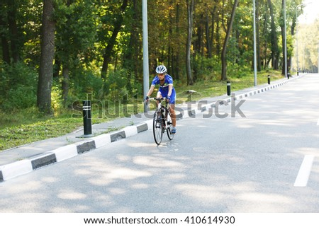 Female sportsman cyclist riding racing bicycle. Woman cycling on countryside summer road or highway. Training for triathlon or cycling competition. - stock photo