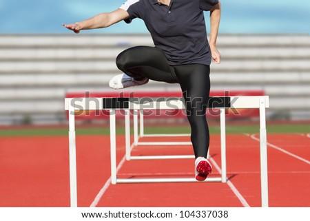 Female sprinter leaps over hurdle - stock photo