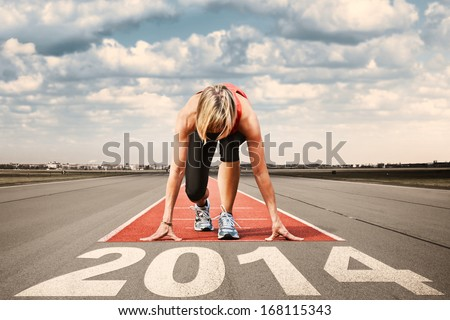 Female sprinter prepares for the start on an airport runway.In the foreground perspective view of  letters 2014.