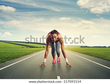 female sprinter standing on the start - stock photo