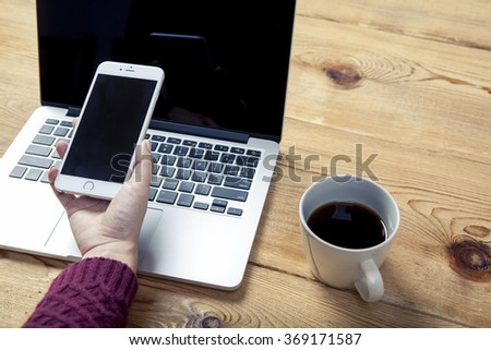 Female staff using laptop and mobile phone