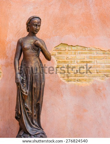 Female statue with grunge wall. - stock photo