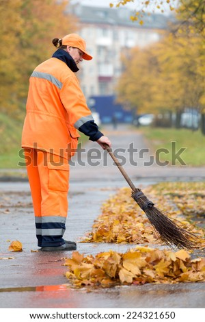 Female street sweeper caretaker cleaning city pavement from dead leaves  - stock photo