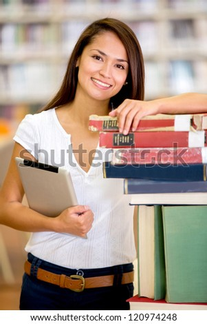 Female student at the library holding a tablet computer - stock photo