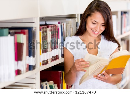 Female student at the library reading a book - stock photo