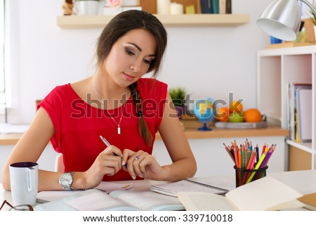 Female student at workplace portrait holding pen and looking in textbooks studying. Woman writing letter, list, plan, making notes, doing homework. Education, self development and perfection concept - stock photo