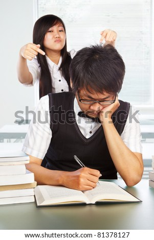 Female student bothering the male student who is still studying - stock photo