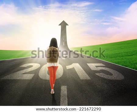 Female student carrying backpack and walk on the road with upward arrow and number 2015 - stock photo