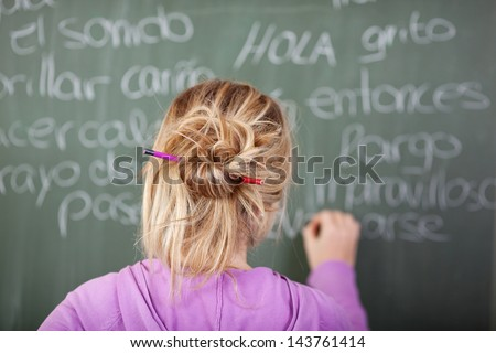 Female student during Spanish class in front of a blackboard with pen in hair - stock photo