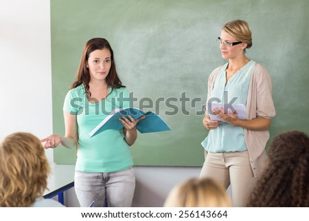 Female student explaining notes besides teacher in the class - stock photo