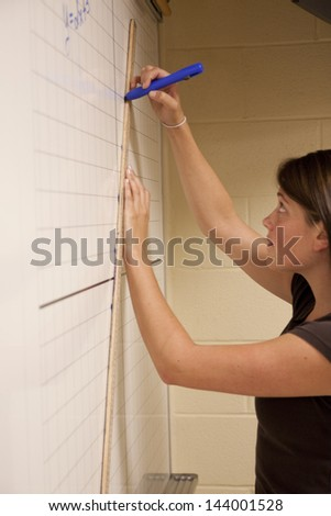 Female student graphing the equation of a line - stock photo