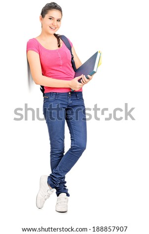 Female student holding books and leaning against a wall isolated on white background