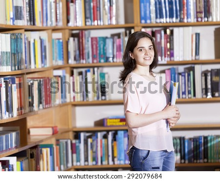 Female student holding notebooks at the university library