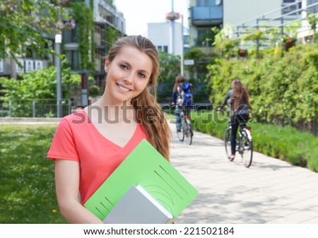 Female student in a red shirt with paperwork on campus