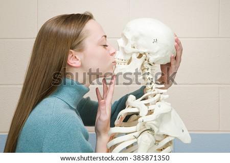 Female student kissing a human skeleton - stock photo