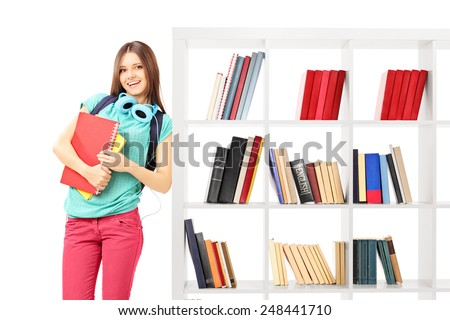 Female student leaning against a bookshelf isolated on white background - stock photo