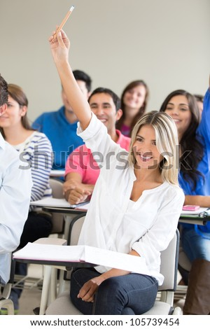 Female student participating in class and raising her hand - stock photo