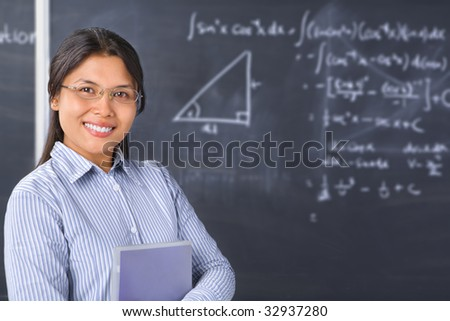 Female student pose in front of blackboard - stock photo