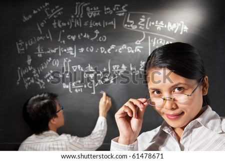 Female student pose  with male student trying to solve the equation on background