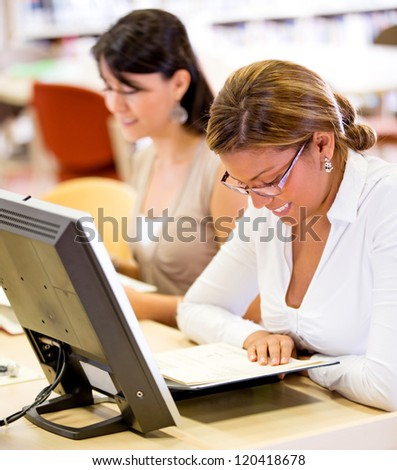 Female student reading a book at the library - stock photo