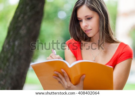 Female student reading a book at the park - stock photo
