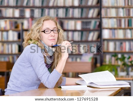 female student reads the book in library. looking at camera