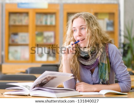 female student reads the book in library. looking away