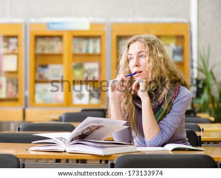 female student reads the book in library. looking away - stock photo