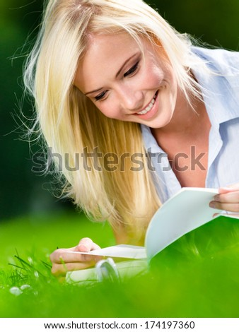 Female student reads the book lying on the green grass