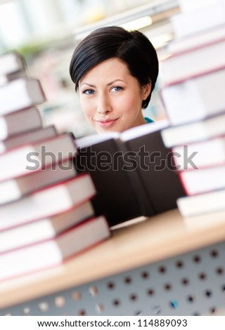 Female student sitting at the desk is surrounded with piles of books. Learning process