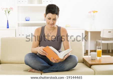 Female student sitting on sofa at home, reading book. - stock photo